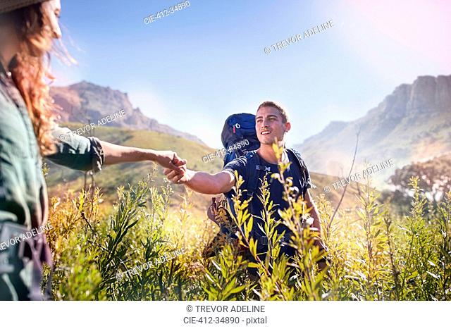 Young couple holding hands hiking in sunny valley