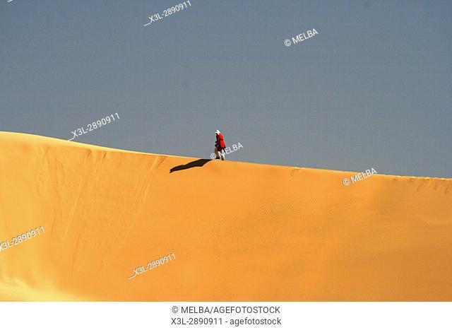 Solitary man walking on a sand dune. In-Akachaker. Tassili Ahaggar. Sahara desert. Algeria