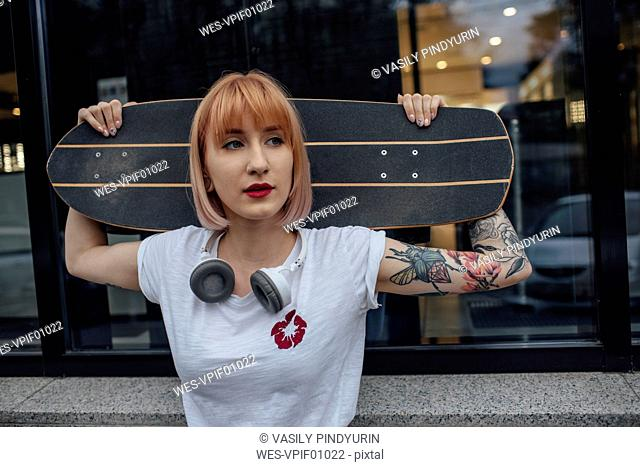 Young woman holding carver skateboard outside a building