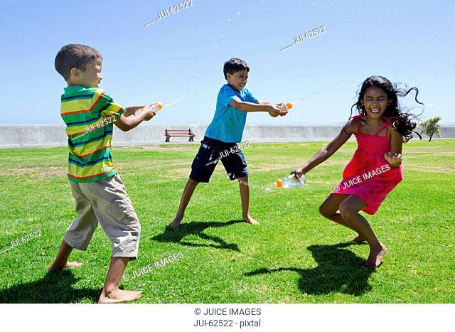 Smiling children having water fight in park