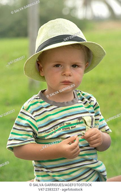 Child in hat looking at camera seriously