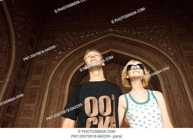 Close-up of a young couple standing and smiling, Taj Mahal, Agra, Uttar Pradesh, India