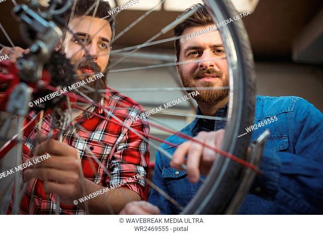 Low angle view of two mechanics repairing a bicycle wheel in their workshop