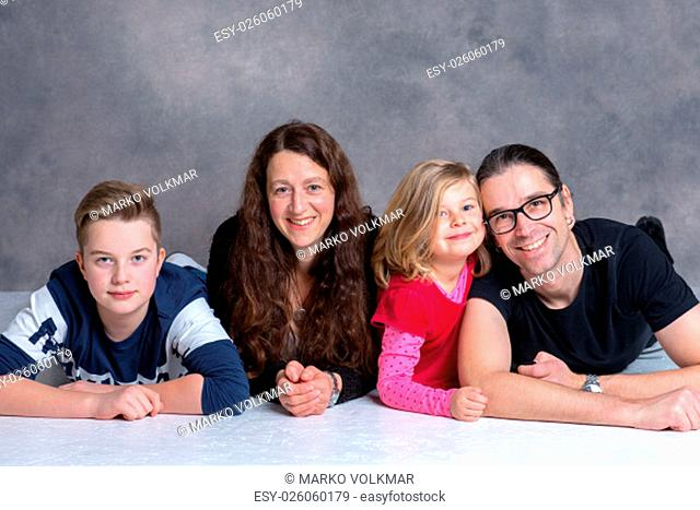 nice family lying on the flor in front of gray background