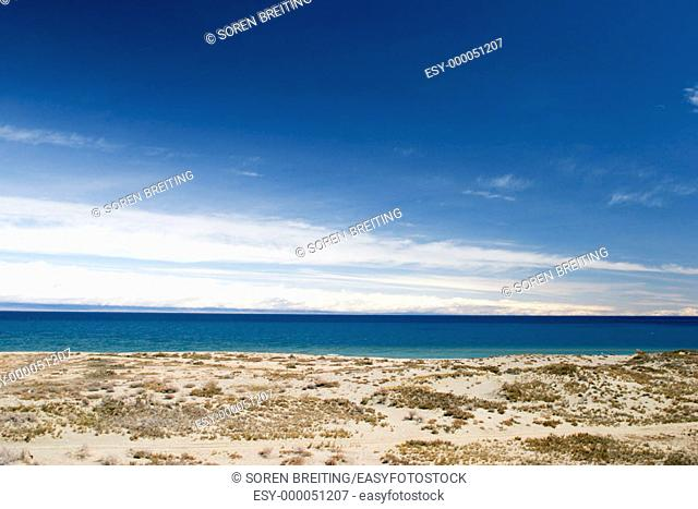 Issyk-Kul Lake, (Ysyk-köl)  in Kyrgyzstan, Central Asia, seen from southern beach, west of Bökönbaev, with dry lands around with xerophytes and snowclad...