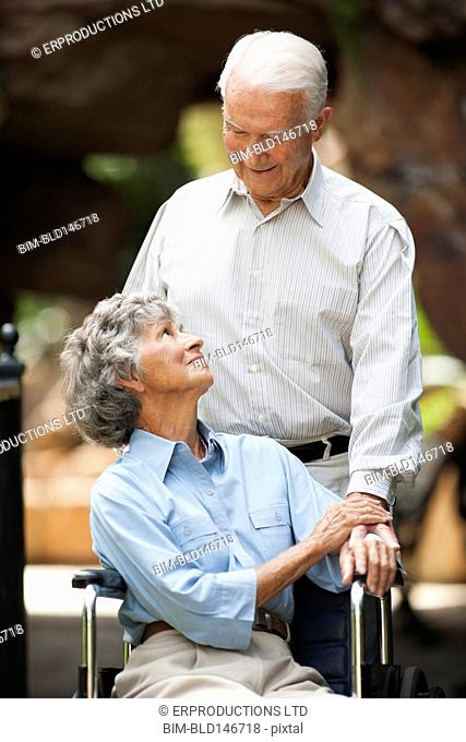 Senior man pushing wife in wheelchair