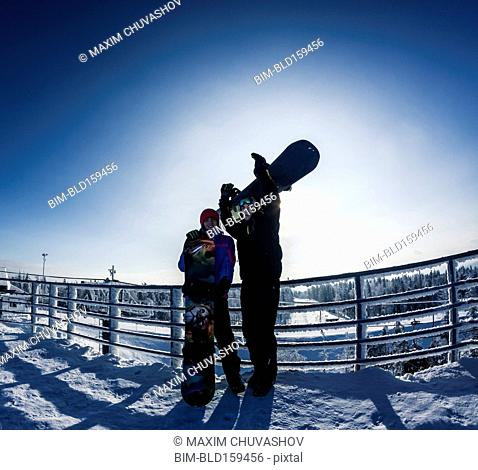 Caucasian snowboarders standing on snowy mountaintop