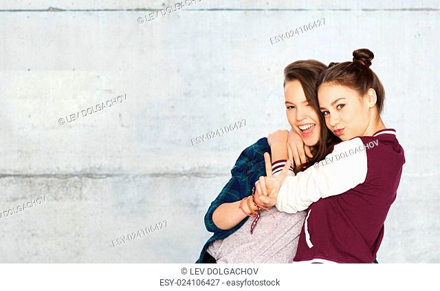 people, friends, teens and friendship concept - happy smiling pretty teenage girls hugging and showing peace hand sign over gray stone wall background