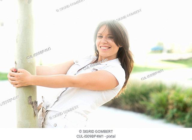 Woman hanging onto tree