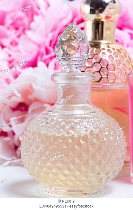 Peony essence in glass vials and fresh peony flowers