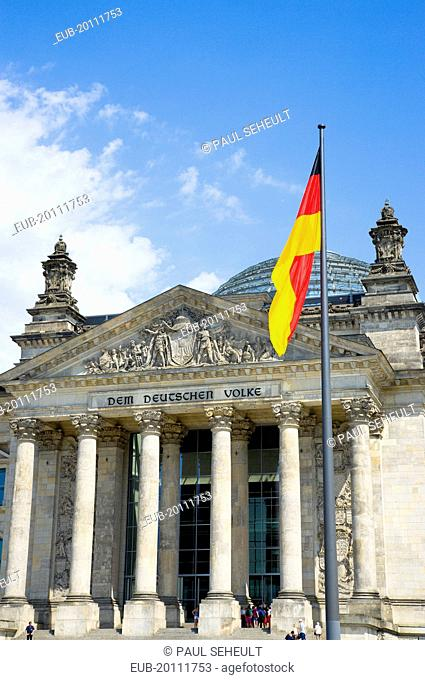 Mitte The Reichstag building in Tiergarten with the inscrption Dem Deucschen Volke For the German People on the facade above the columns at the entrance with a...