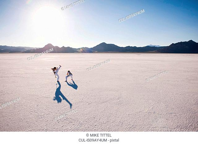 Elevated view of two women performing capoeira on Bonneville Salt Flats, Utah, USA