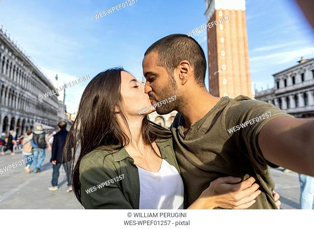 Italy, Venice, selfie of tourist couple kissing on St Mark's Square