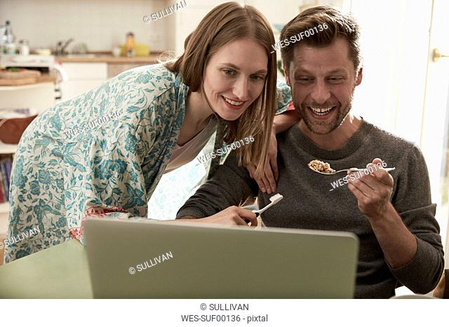 Happy couple looking at laptop together
