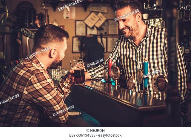 Handsome bartender pouring a pint of beer to customer in a pub
