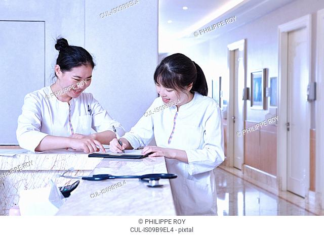 Medical professionals at hospital reception desk using digital tablet
