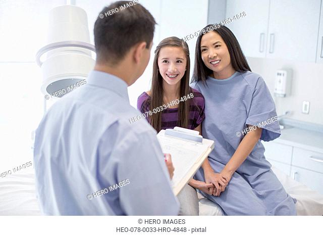 mother and daughter talking with doctor in radiology room