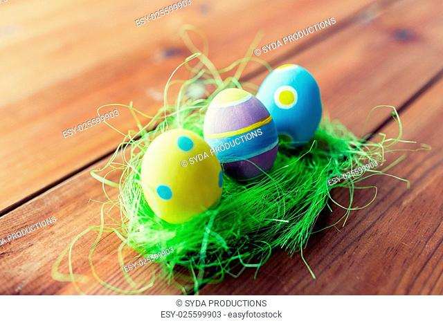 easter, holidays, tradition and object concept - close up of colored easter eggs and decorative grass on wooden surface