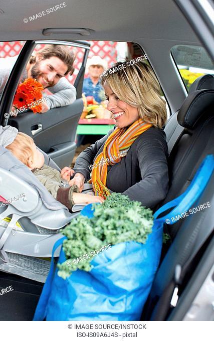 Woman buckling son in car seat