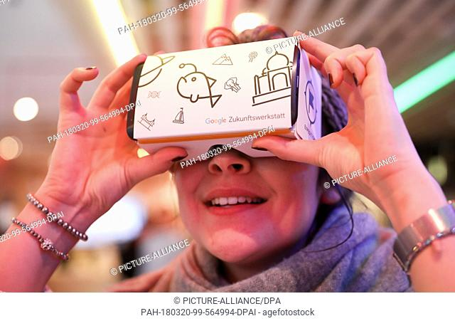 20 March 2018, Germany, Hamburg: A young woman looking into a pair of Google virtual reality glasses before a press conference for the Google future workshop...