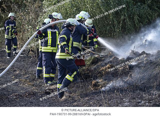 31 July 2019, North Rhine-Westphalia, Quetzen: Firefighters are fighting an extensive fire that had started on a stubble field and then jumped onto a slope