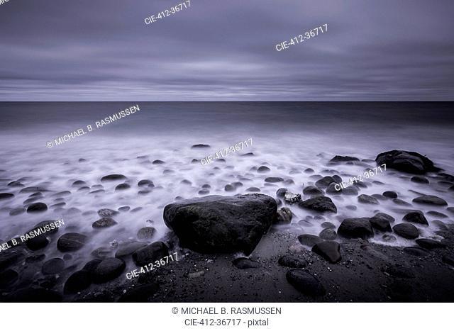 Tranquil overcast gray seascape and rocks on beach, Kalundborg, Denmark