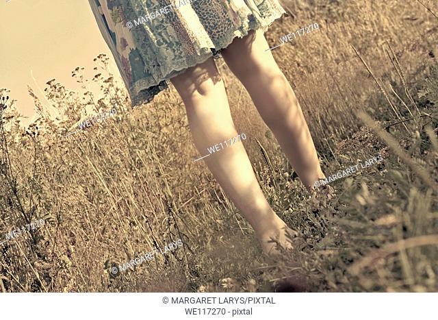 Legs of beautiful girl in a blue dress walking barefoot in the meadow