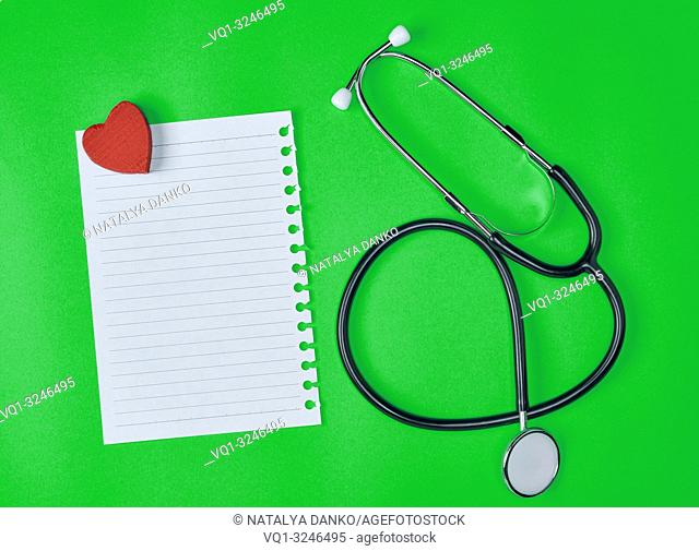 empty white piece of paper in a line and a medical stethoscope on a green background