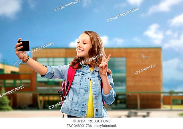 girl taking selfie by smartphone over school