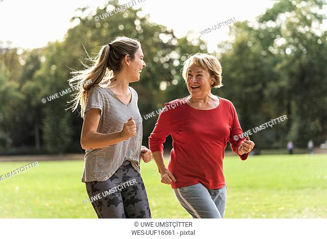 Granddaughter and grandmother having fun, jogging together in the park