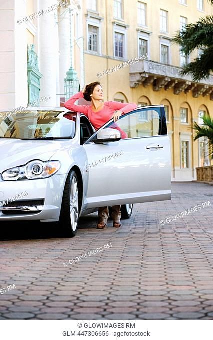 Woman leaning against a car and thinking, Biltmore Hotel, Coral Gables, Florida, USA