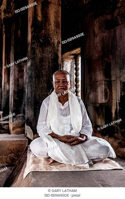 Senior buddhist monk meditating in temple in Angkor Wat, Siem Reap, Cambodia