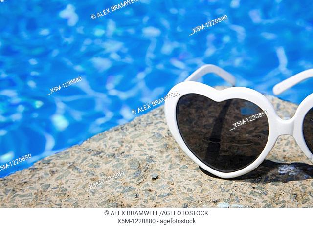Heart shaped sunglasses by a bright blur swimming pool
