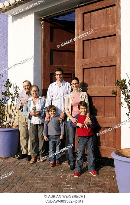 Multi-generational family standing at front door, smiling, portrait