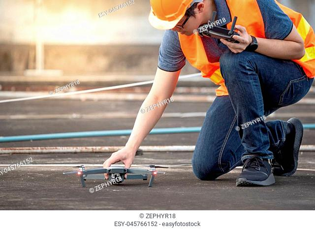 Young Asian engineer using drone at construction site. Using unmanned aerial vehicle (UAV) for land and building site survey in civil engineering project