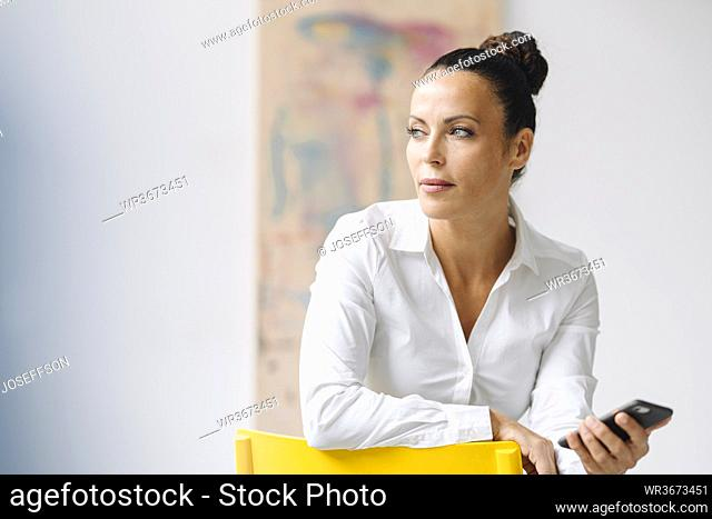 Thoughtful businesswoman holding smart phone looking away while sitting on chair in home office