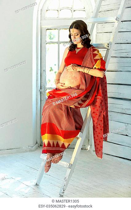 Indian picture on woman mehendi tradition decoration, resistant design by special paint, brown henna. Woman sitting in indian red dress on white wooden...