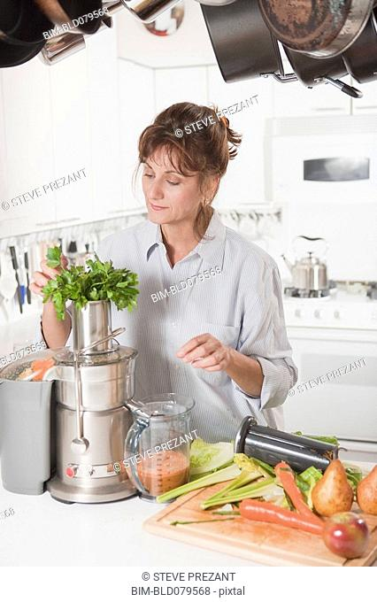 Caucasian woman juicing vegetables in kitchen
