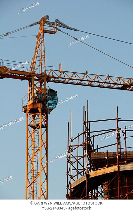 yellow crane and scaffolding on building construction site in rome italy