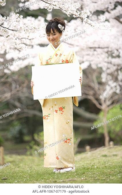 Japanese Woman Standing Holding White Board