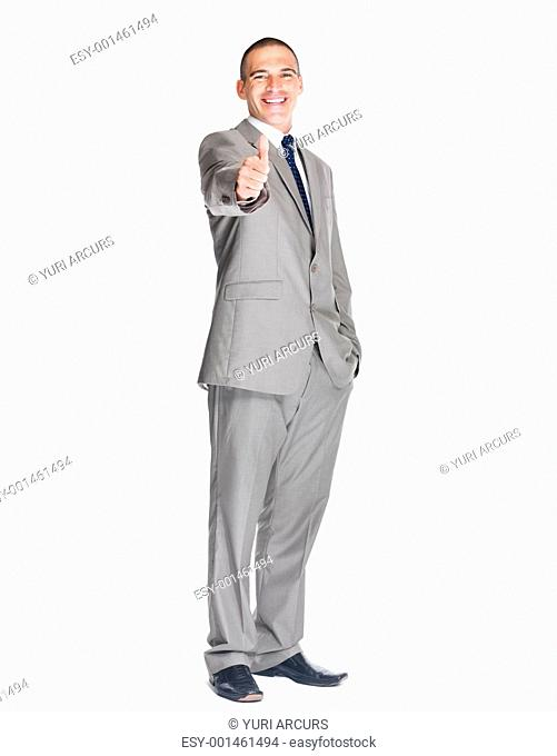 Portrait of a confident young male business executive showing thumbs up sign against white background