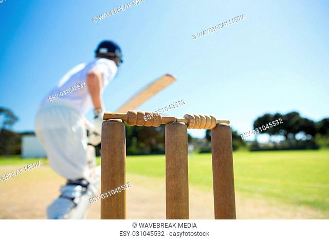 Close up of wooden stump by batsman standing on field
