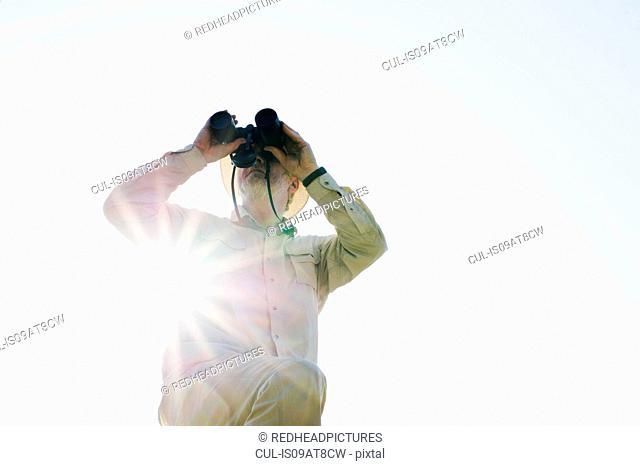 Low angle view of senior man in sunlight looking through binoculars