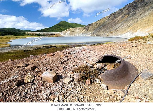 Remains of old Japanese sulphur plant and lake in caldera of Golovnino volcano on Kunashir Island in Kuril Island chain in Russia