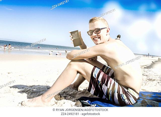 Holiday portrait of a young man in 20s updating social media phone status when relaxing at a Queensland beach. Technology smart teens