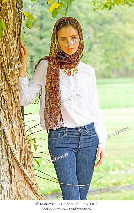Young woman standing under tree. Woman in a dark scarf with white blousee and blue jeans stands under a large old tree