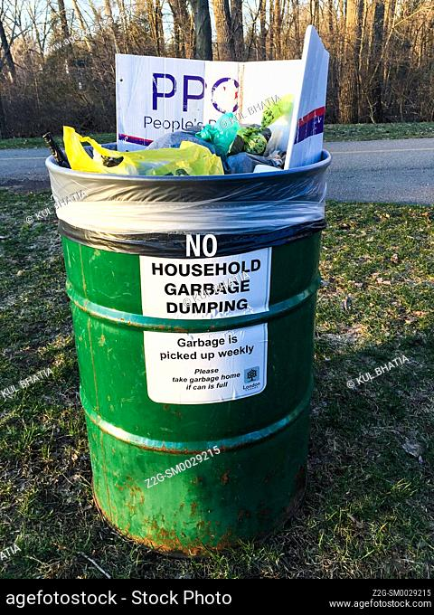 An open garbage can with a warning against dumping household garbage, Ontrio, Canada