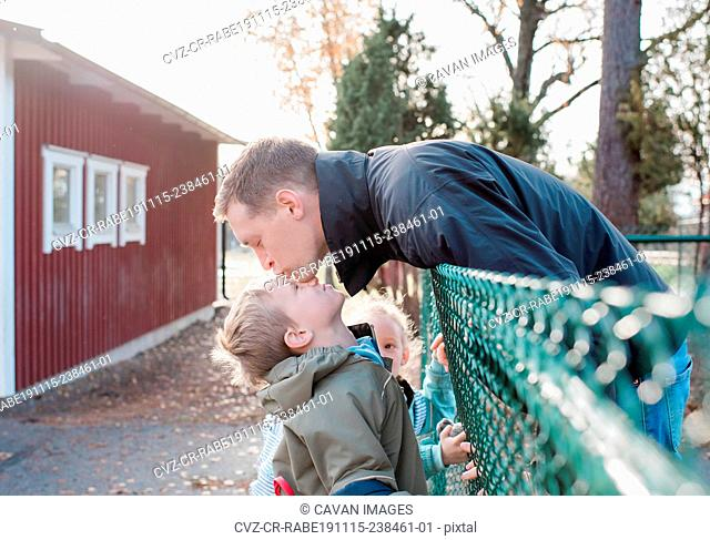 father kissing his son goodbye at the school gate