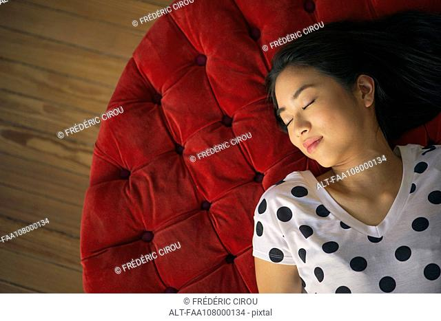 Young woman resting on ottoman