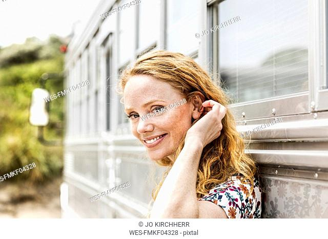 Portrait of smiling woman at an old bus